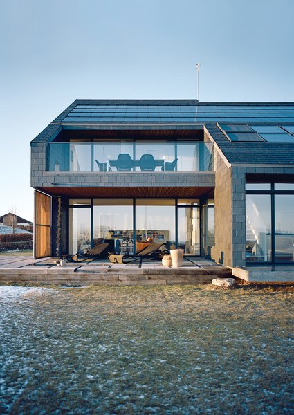 While the slate-clad northern facade has few windows and a steeply pitched roof, the southern facade is dominated by glass with the solar-panel-clad roof strategically angled to catch the sun.