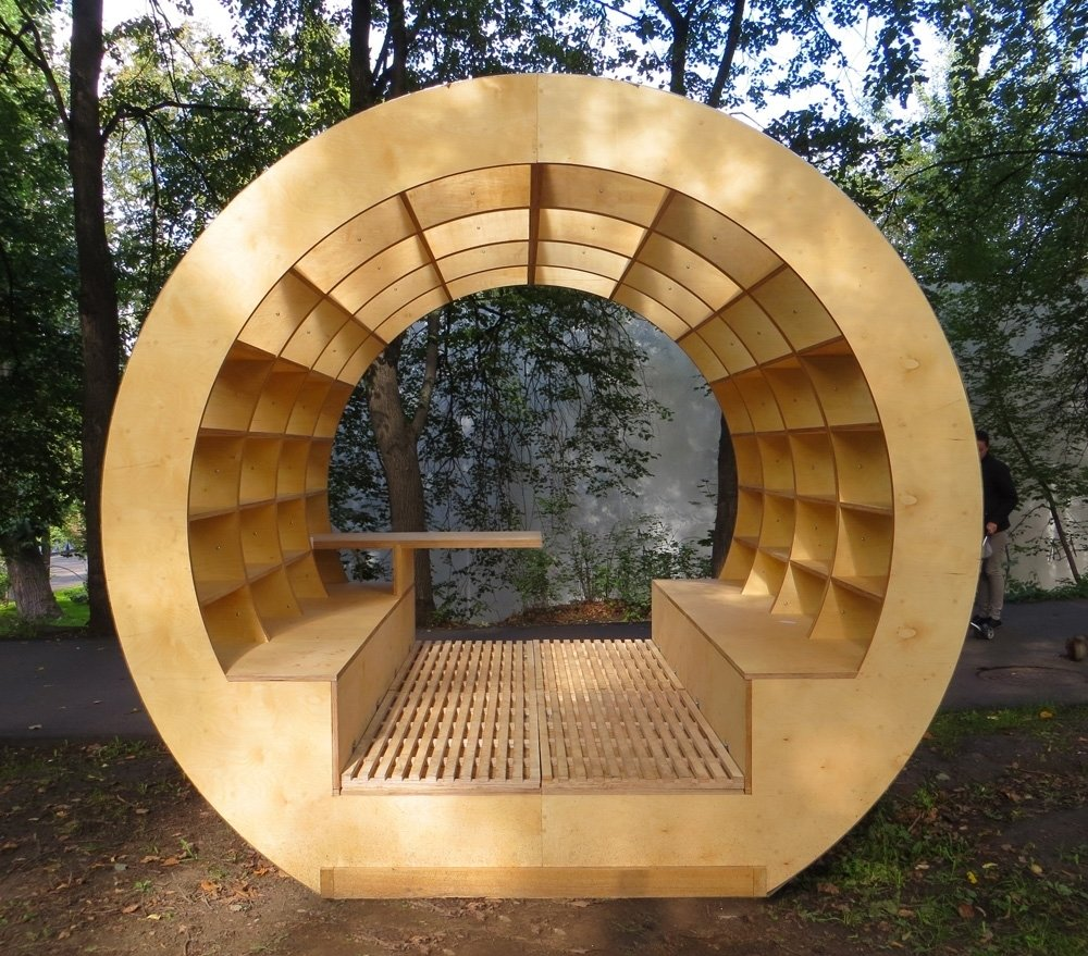 This outdoor bench-bibliotheque brings new meaning to the phrase 'surrounded by books.' Promising to bring intellectuals outdoors, this gazebo features a small table for lunch or tea, and easy-to-clean slatted wooden floors. Photo courtesy of Ruetemple Architectural Studio.  Innovative Outdoor Libraries in Russia by Jacqueline Leahy