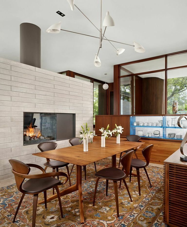 The interior combines modern and more traditional elements, such as this oriental rug. Tagged: Dining Room, Table, Chair, Pendant Lighting, Rug Floor, and Standard Layout Fireplace.  Photo 5 of 7 in A Sensitive Modern House in Austin, Texas