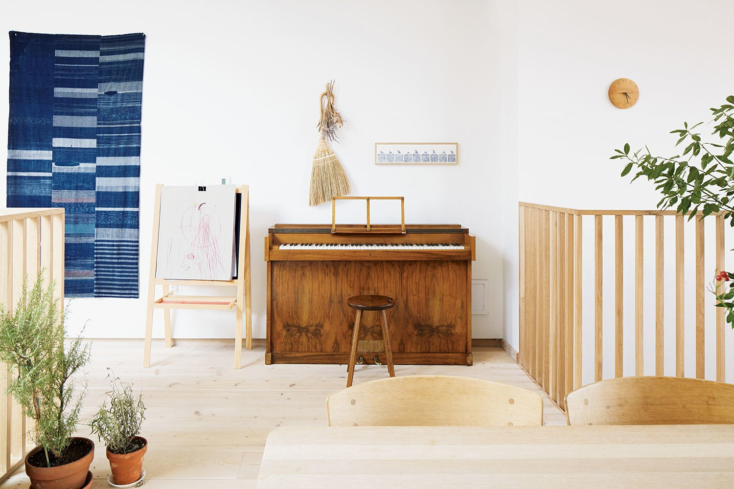 An antique Japanese indigo tapestry hangs by a vintage Danish piano. Tagged: Hallway and Light Hardwood Floor.  Photo 2 of 10 in These Shop Owners Have a Killer Apartment Right Upstairs