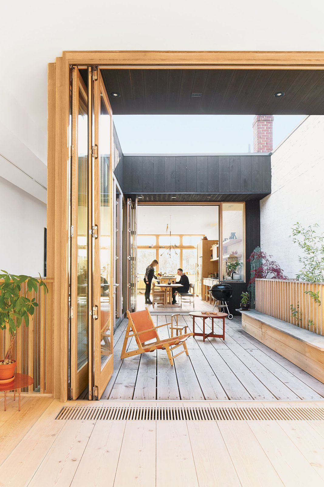 A third-floor courtyard stands in for a backyard and gives Elodie, the couple's two-year-old daughter, a place to play outdoors. A Hunting chair by Børge Mogensen shares the space with a child's chair by   Tomii Takashi and a vintage Danish coffee table.  Photo 4 of 10 in These Shop Owners Have a Killer Apartment Right Upstairs
