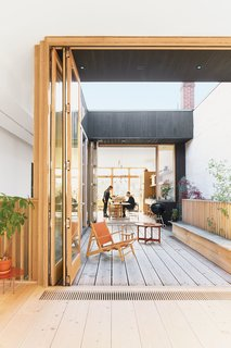 A third-floor courtyard stands in for a backyard and gives Elodie, the couple's two-year-old daughter, a place to play outdoors. A Hunting chair by Børge Mogensen shares the space with a child's chair by Tomii Takashi and a vintage Danish coffee table.