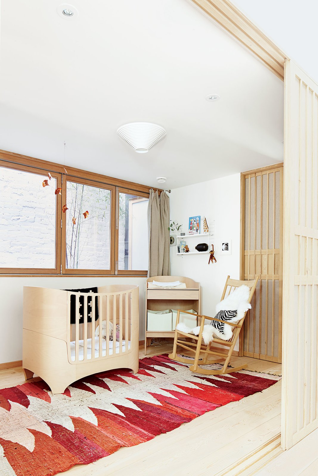 A copper mobile by JF Jones hangs over a Leander crib and a vintage Moroccan rag rug in the nursery. The rocking chair is by Hans Wegner for Fredericia. Tagged: Kids Room, Bed, Bedroom, Light Hardwood Floor, Toddler Age, Rockers, and Neutral Gender.  Photo 6 of 10 in These Shop Owners Have a Killer Apartment Right Upstairs