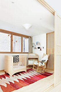 How-To Design with Patterned Rugs - Photo 2 of 7 - A copper mobile by JF Jones hangs over a Leander crib and a vintage Moroccan rag rug in the nursery. The rocking chair is by Hans Wegner for Fredericia.