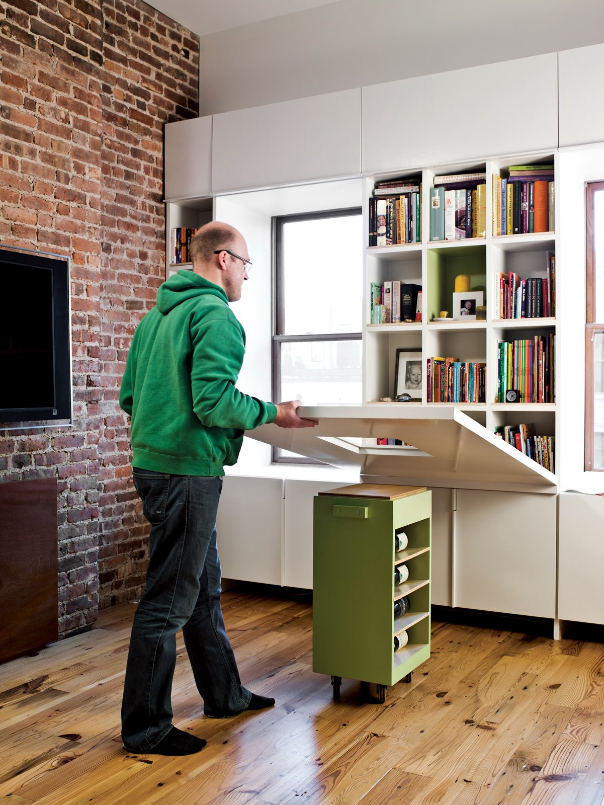 When it's time to eat or do homework, the adults lower the tabletop, revealing a dozen book cubbies.  Storage by Dwell from Storage-Smart Renovation in New York City
