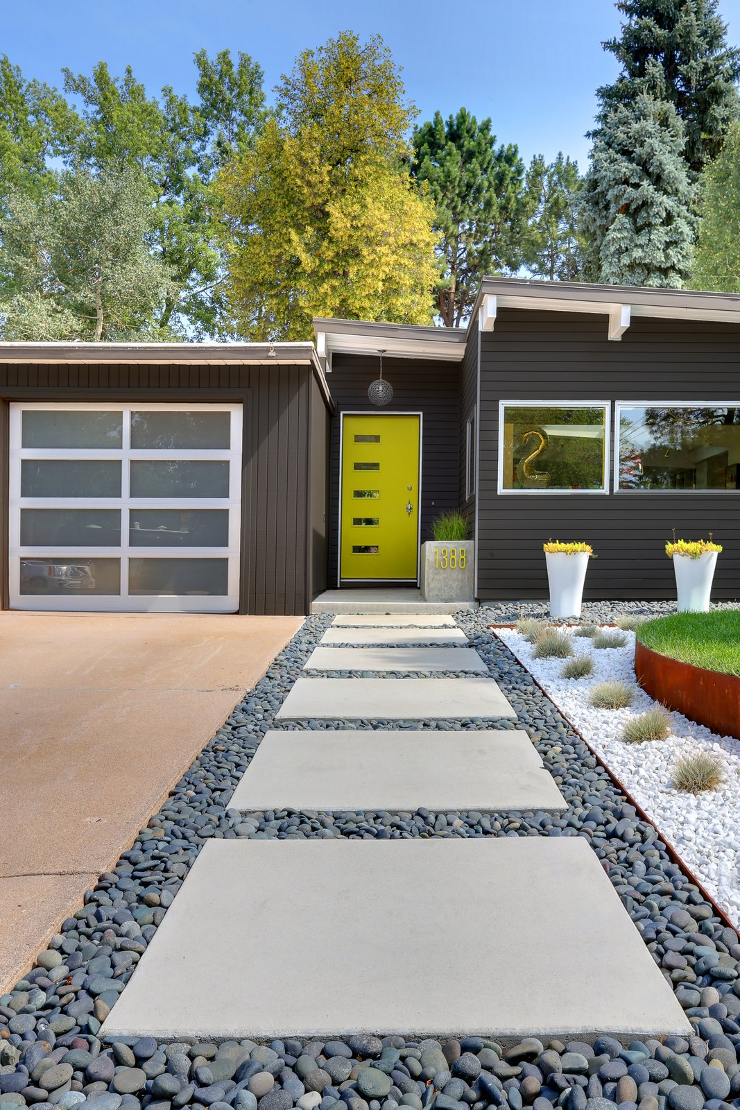 Generous concrete pavers lead to the entrance. The home's angles are typical of the midcentury homes in the neighborhood. Modern Homes in Colorado by Luke Hopping