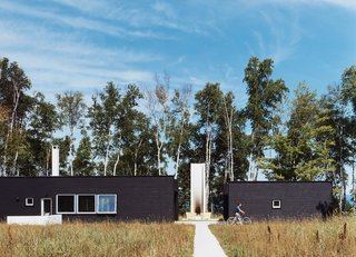15 Modern Homes with Black Exteriors - Photo 4 of 15 - Two Black Sheds incorporates all the conventional aspects of a weekend retreat in a rather unconventional way.