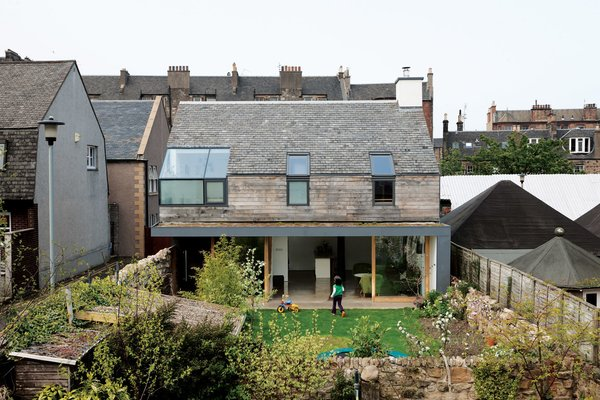 The framed aluminum of the corner window by Natralight breaks up the roof of recycled slate tiles, which is entirely of a piece with the roofs around it. The Scottish oak cladding comes from Abbey Timber and the black aluminum cladding from MSP Scotland.