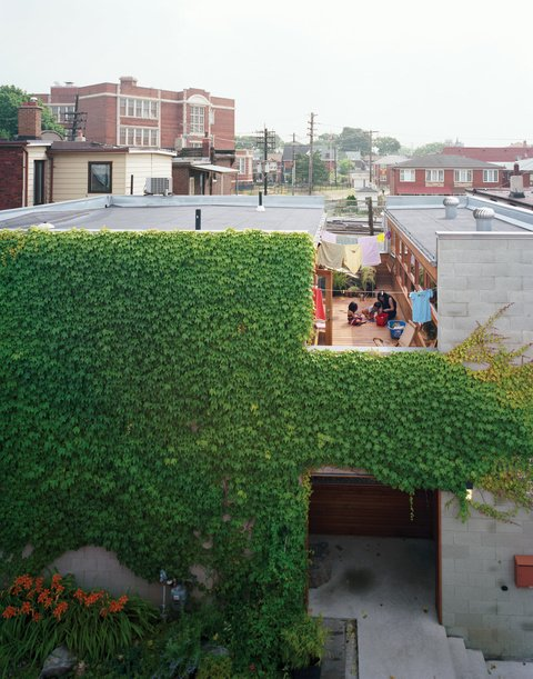 A wide cut across the top of the structure made room for a second-floor courtyard where the family can catch some sun but maintain their privacy. On the ground level, the front door is tucked into an ivy-covered alcove lined with ipe, a material used throughout the house. Photo by: Juliana Sohn 20+ Modern Warehouse and Garages Conversions by Zachary Edelson