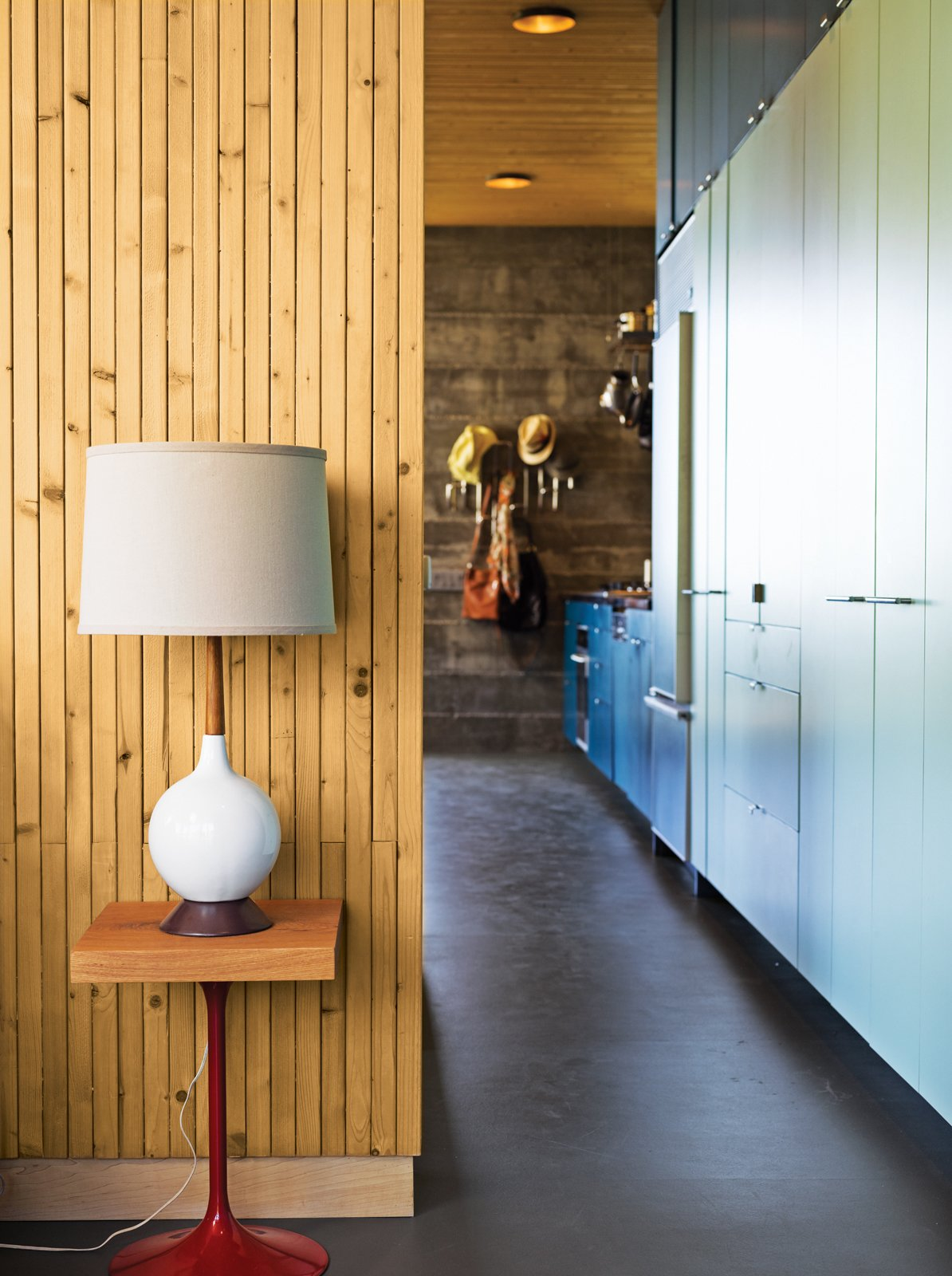 Working with a limited footprint, a daunting slope, and killer views, architect Bruce Bolander went vertical with a secluded canyon house in Malibu. A colorful, laminate-clad wall of storage stretches seamlessly from the kitchen to the bedroom, where a repurposed speaker stand serves as the bedside table. Photo by J Bennett Fitts. Tagged: Living Room, Table Lighting, and Concrete Floor.  Photo 1 of 9 in Malibu Canyon House with a View