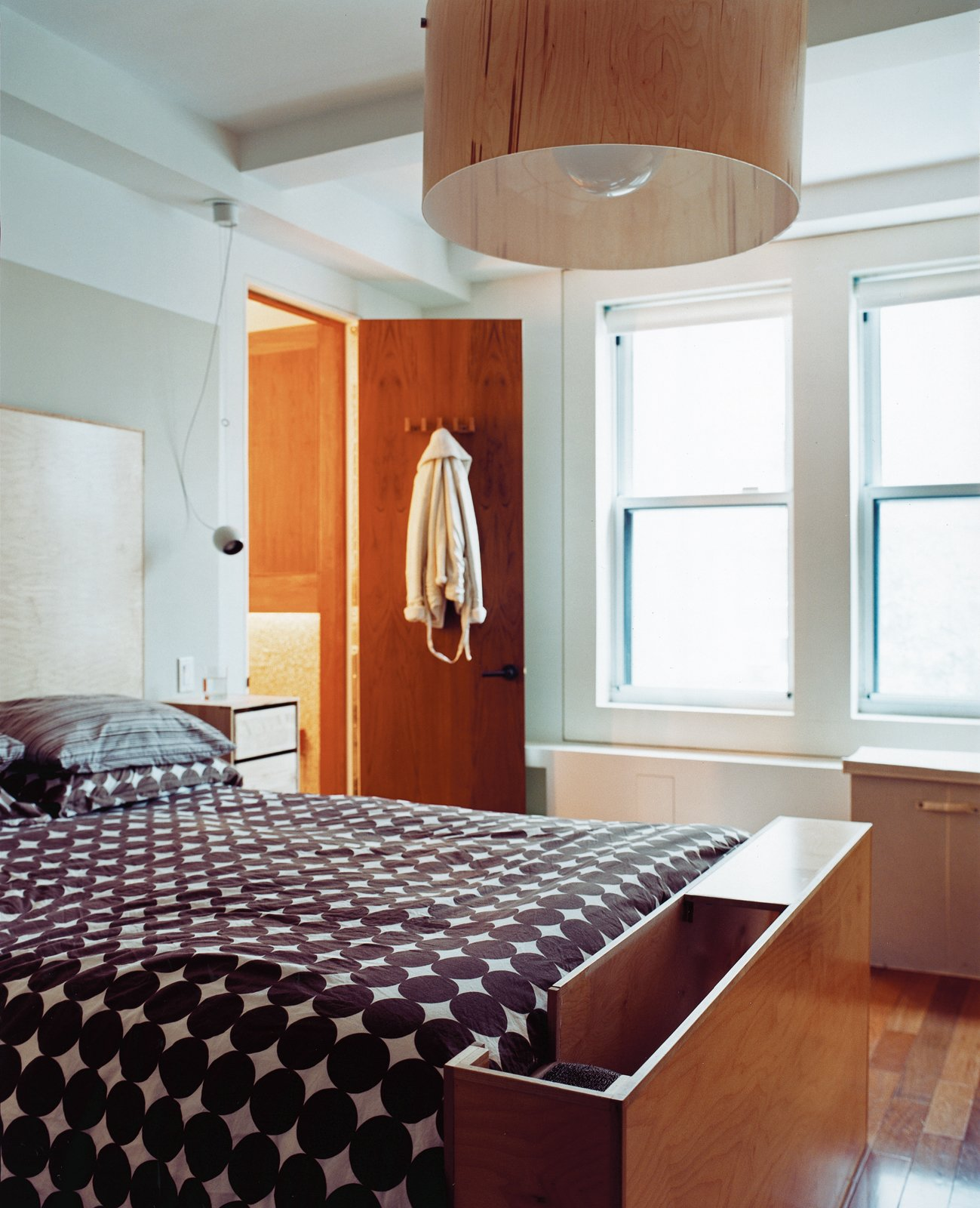 The master bedroom has a custom ramp for the dachshund at the foot of the bed and an oversize birch-veneer pendant lamp. The bedside tables are actually CD cases affixed to the wall.  Photo 2 of 11 in Outdoor Living in NYC