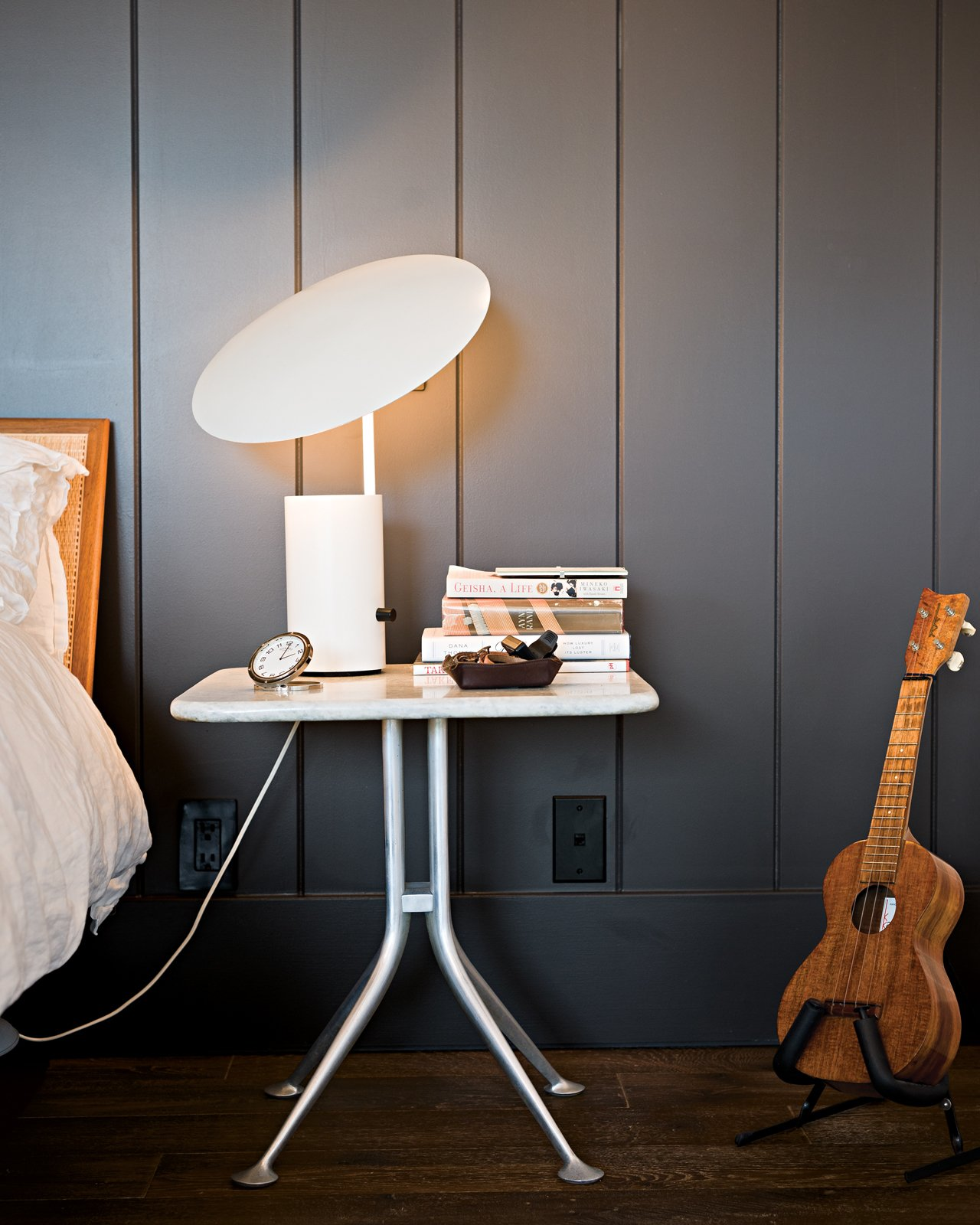 More prized possessions that made the cut: A George Nelson Half-Nelson lamp sits atop an Alexander Girard bedside table. Tagged: Bedroom, Night Stands, Table Lighting, and Dark Hardwood Floor.  Photo 6 of 18 in Less is More in this Manhattan Beach Bungalow