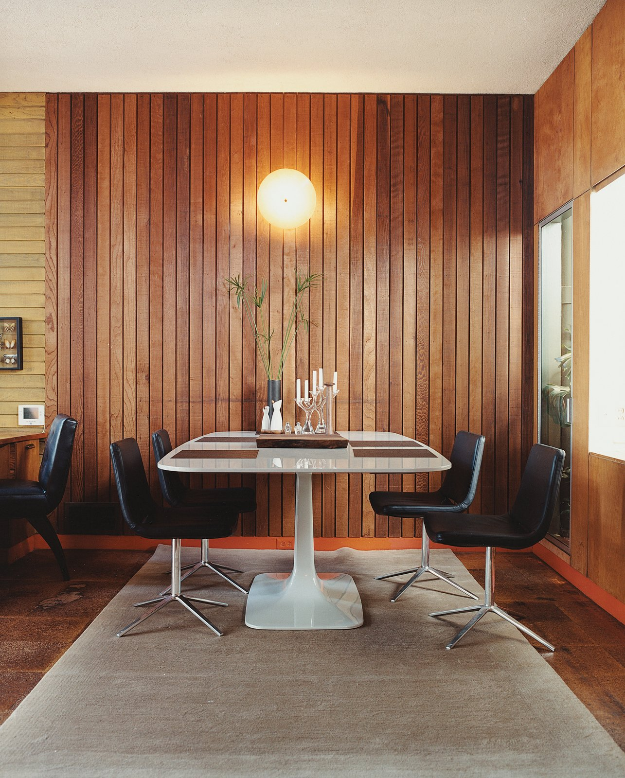 In the dining area, Metropolitan side chairs by Jeffrey Bernett for B&B Italia surround a Surf Table designed by Carlo Colombo for Zanotta. Tagged: Dining Room, Chair, Table, Porcelain Tile Floor, and Wall Lighting.  Midcentury Homes by Dwell from Mid-Century Mash-Up