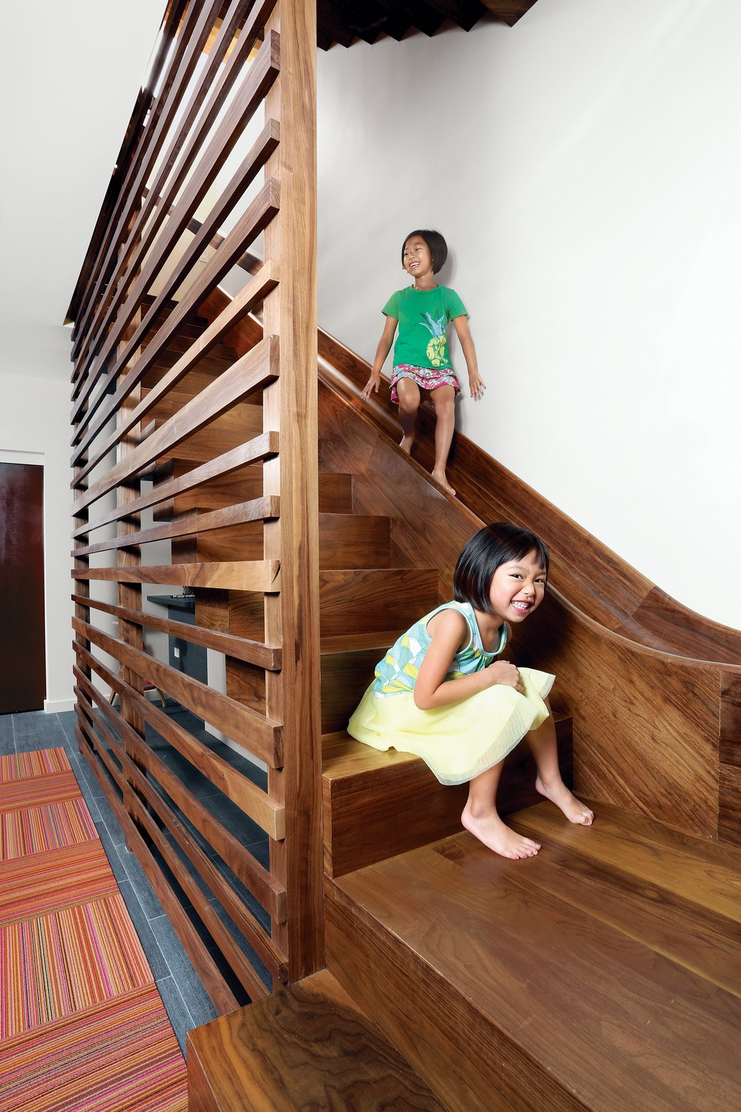 "The walnut staircase and slide in a Chicago town house leads from the main level to the basement. To protect people on the ride down, a ""crash pad"" fashioned from a standard gymnastic mat covers the wall at the slide's base. Tagged: Staircase, Wood Tread, and Wood Railing.  Lakeview by Diana Budds"