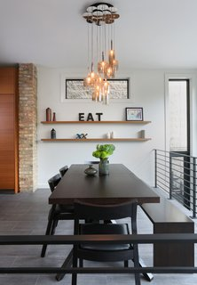 Julie Fisher on How to Shop for Furniture - Photo 1 of 2 - In the dining room, Fisher opted for a Cross Extension table and Profile chairs from Design Within Reach and a custom bench by JJ Woodwork. The Spillray pendants are by Axolight.