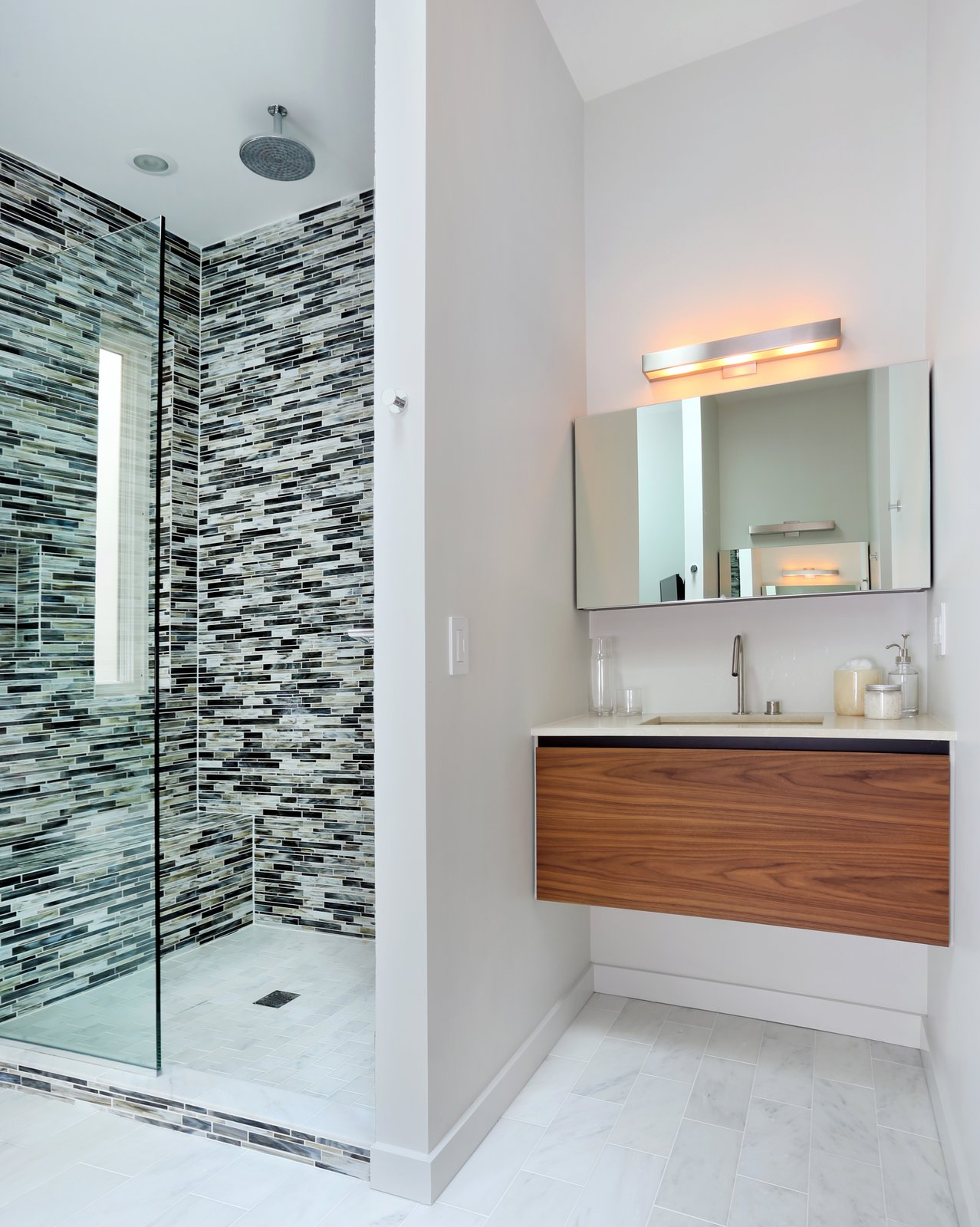 In the master bathroom, glass tile clads the shower and Carrara marble lines the floor. The shower fixtures are Hansgrohe.