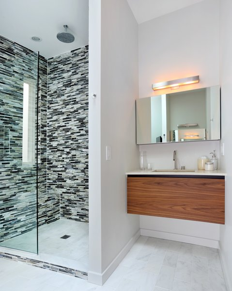 In the master bathroom, glass tile clads the shower and Carrara marble lines the floor. The shower fixtures are Hansgrohe. Photo 7 of Lakeview modern home