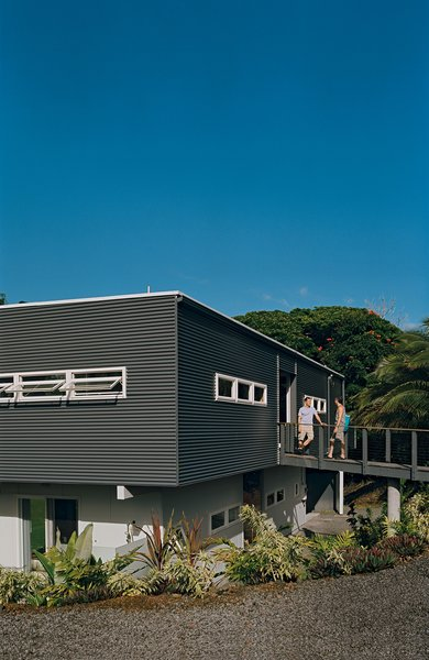 Mike Kurokawa and Paul Fishman set out for the beach from their house in the Puna region of Hawaii. A bridge leads from street level to the upper floor of the house, which is situated in a natural depression, or kipuka.