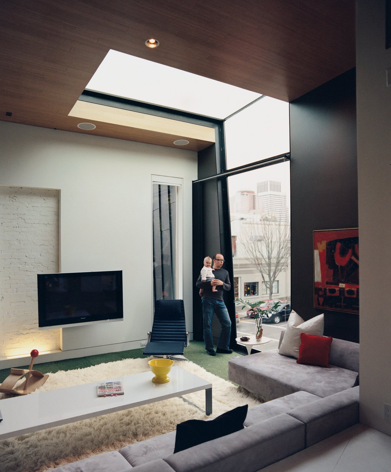 In the living room, a double-height window and a skylight work together to frame a view of the Victorian Gothic church just across the street. Tagged: Living Room, Sectional, and Rug Floor. Show-Stealing Skylights in Modern Homes by Zachary Edelson