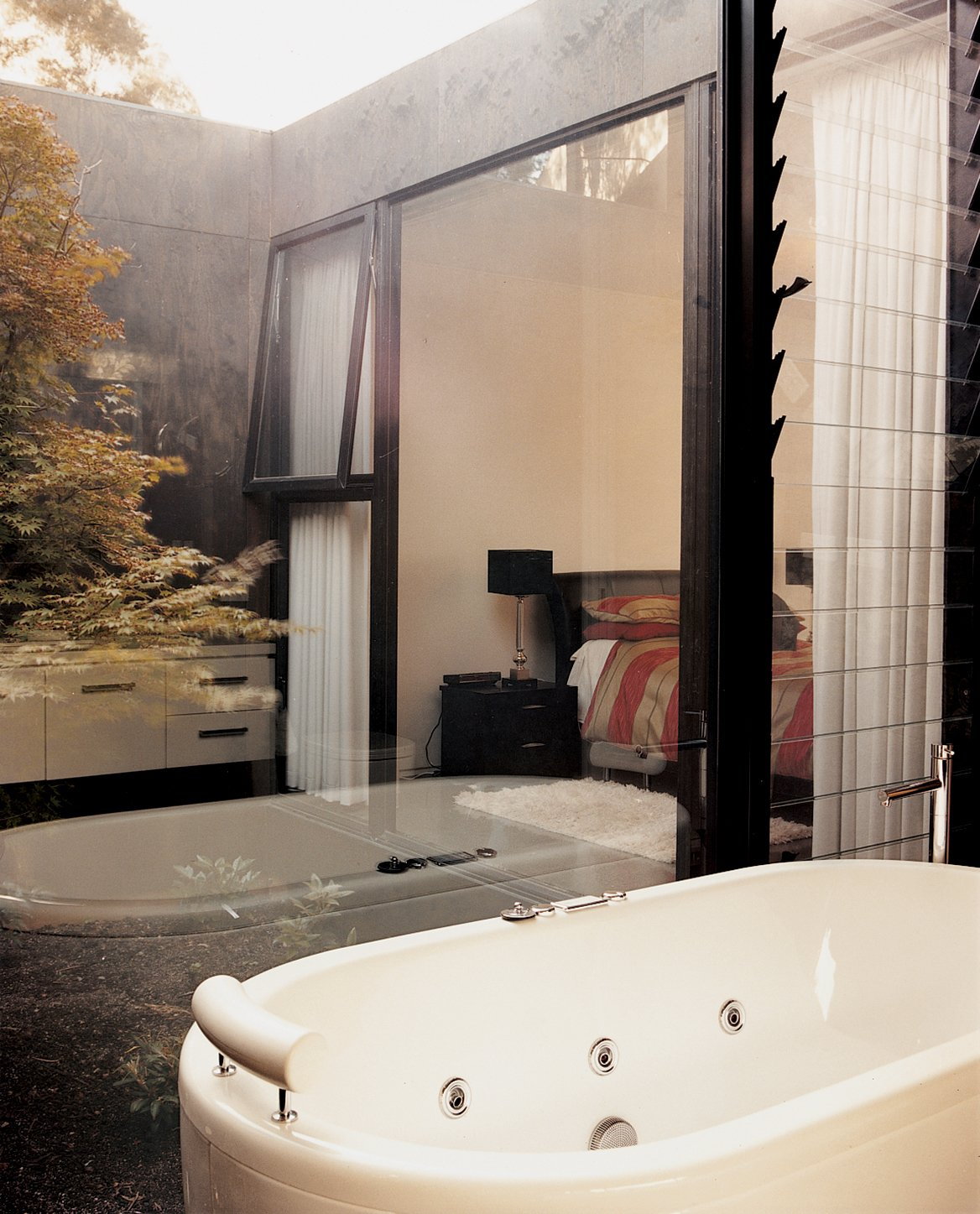 """The guest bathroom  includes glass walls that look out onto one of the house's """"voids,"""" in which pear trees grow.  Photo 8 of 12 in Kingston Brio"""