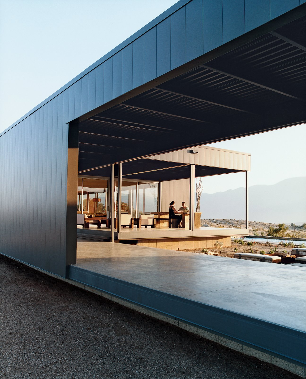 Leo Marmol and Alisa Becket enjoy one of their home's many outdoor spaces. Tagged: Exterior, House, Metal Roof Material, Metal Siding Material, and Flat RoofLine.  Photo 1 of 9 in Desert Utopia