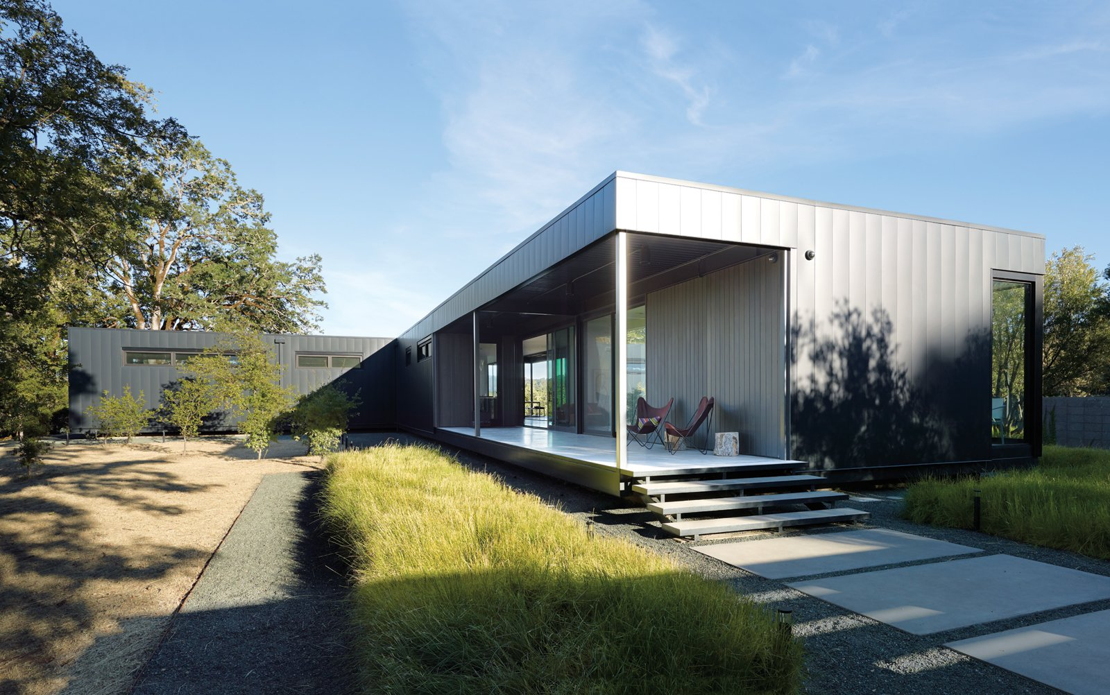 "When Abbie and Bill Burton hired Marmol Radziner to design their prefab weekend home, their two requests were ""simple-simple, replaceable materials,"" says Abbie—such as concrete floors (poured offsite in Marmol Radziner's factory) and metal panel siding—and ""the ability to be indoors or outdoors with ease."" Deep overhangs provide shade and protection from rain, so the Burtons can leave their doors open year-round and hang out on their 70-foot-long deck even in inclement weather. They visit the house once a month, usually for a week at a time, with Vinnie and Stella, their rescue Bernese Mountain dogs. Their two adult children occasionally join them. The couple hopes to one day retire here. Tagged: Outdoor and Front Yard.  Exteriors by Matthew Keeshin from A Simple Plan"
