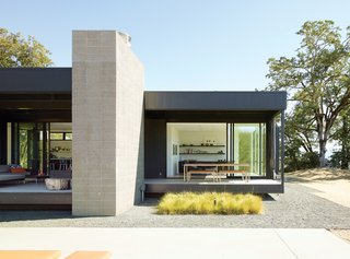 "7 Glorious Golden State Prefabs - Photo 1 of 7 - When Abbie and Bill Burton hired Marmol Radziner to design their prefab weekend home, their two requests were ""simple-simple, replaceable materials,"" says Abbie—such as concrete floors (poured offsite in Marmol Radziner's factory) and metal panel siding—and ""the ability to be indoors or outdoors with ease."" Deep overhangs provide shade and protection from rain, so the Burtons can leave their doors open year-round and hang out on their 70-foot-long deck even in inclement weather."