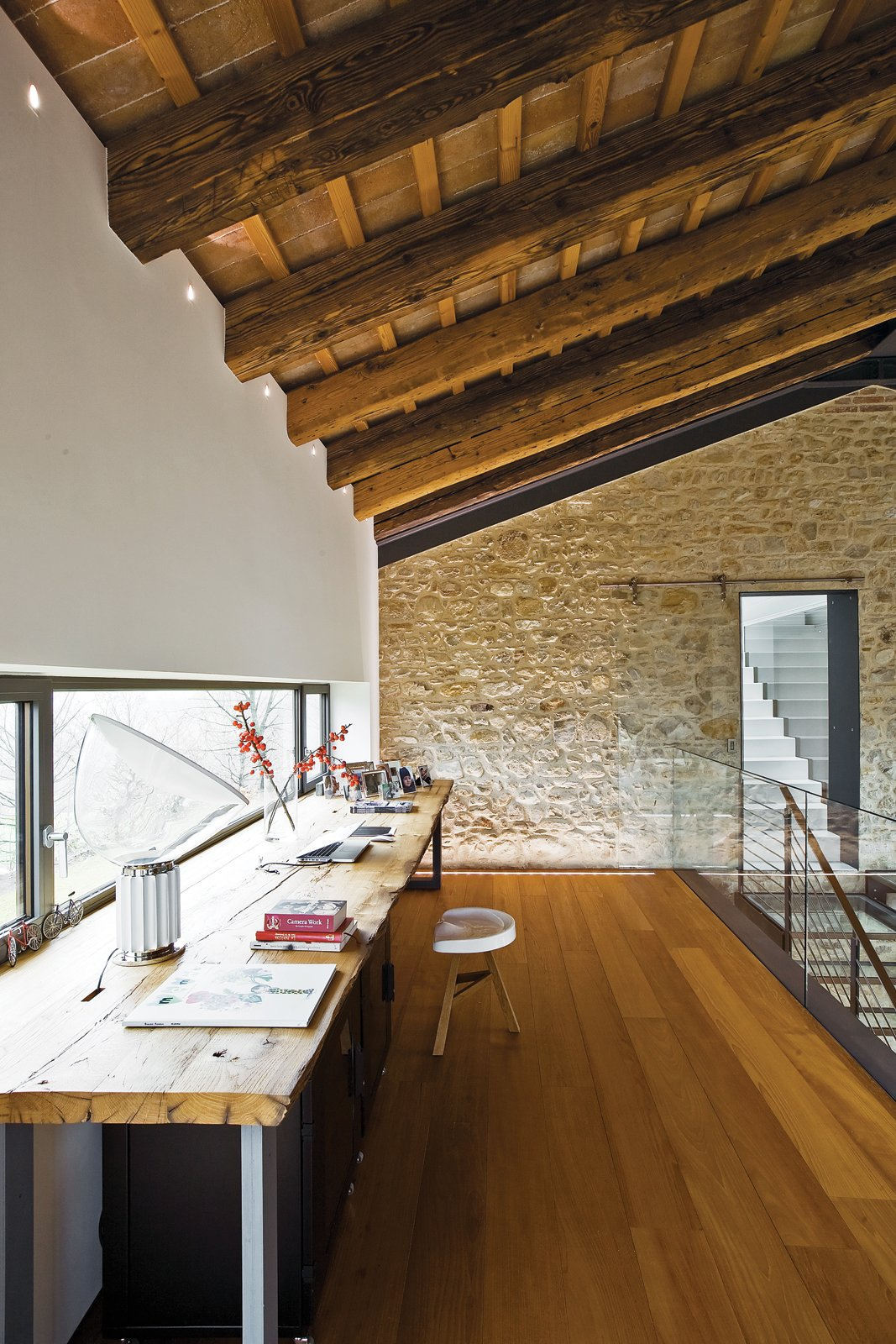 """""""At first we thought we might not need that much space, but then we started thinking long term. We look at this house as the home of our lifetime."""" —Guido Chiavelli Tagged: Office, Chair, and Medium Hardwood Floor.  Photo 9 of 13 in A Renovated Farmhouse in Northern Italy"""