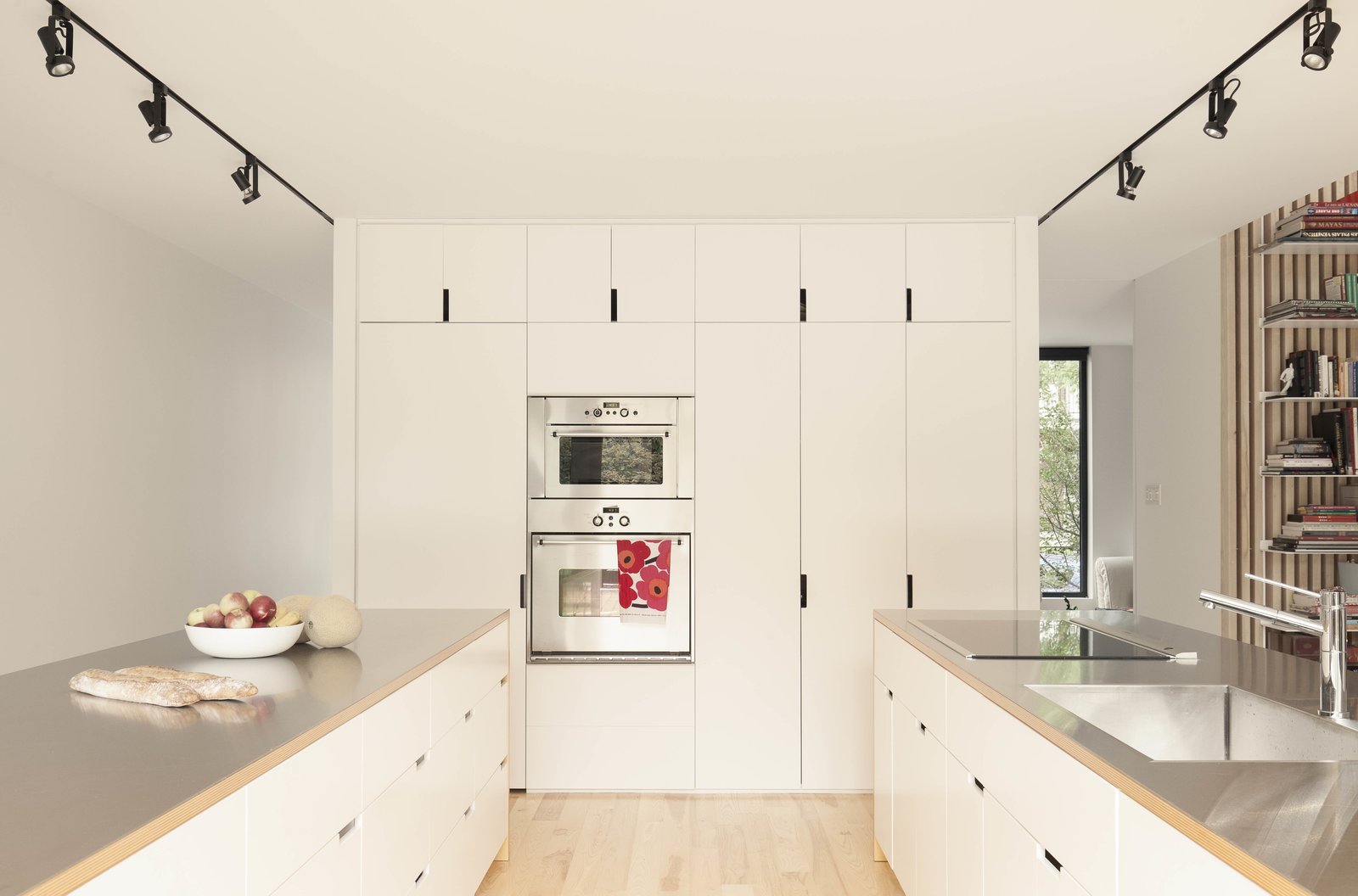 The twin kitchen islands are oriented parallel to the living room. The cabinet fronts are finished in white lacquer, with stainless-steel counters atop ash veneer.
