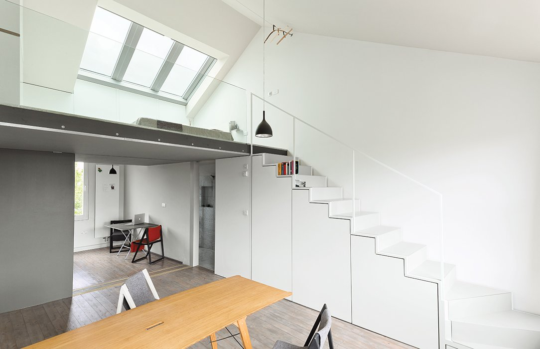 Hynam designed and built the cabinets under the stairs and a drawer that slides out from beneath the bottom step. Drink H1 pendant lamps from Rotaliana hang in the kitchen and above a Grassworks dining table by Jair Straschnow.  190+ Best Modern Staircase Ideas by Dwell from This Is How You Can Live Large in a Small Space