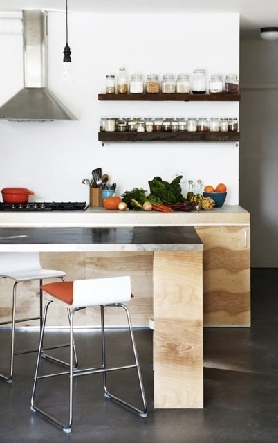 The kitchen has open storage and cabinets and an island made of plywood.  Kitchen by Madainn Jonah Krall from A Modern House on a Budget in Los Angeles