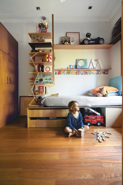 Tom's compact bedroom feels much larger thanks to interlocking shelves and storage. The plywood bed and surrounding shelving were custom-built by Wilkin and a hired carpenter.