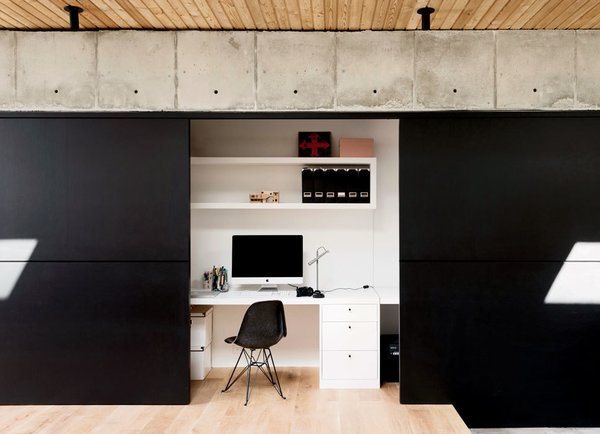 Located off of the kitchen, Vivi's office disappears behind sliding walls covered in black chalkboard paint from Behr. Tagged: Office, Chair, Desk, and Shelves.  Apartment of My Dreams by Meg Dwyer from A Texas Couple Builds Their Cast-In-Place Concrete Dream Home