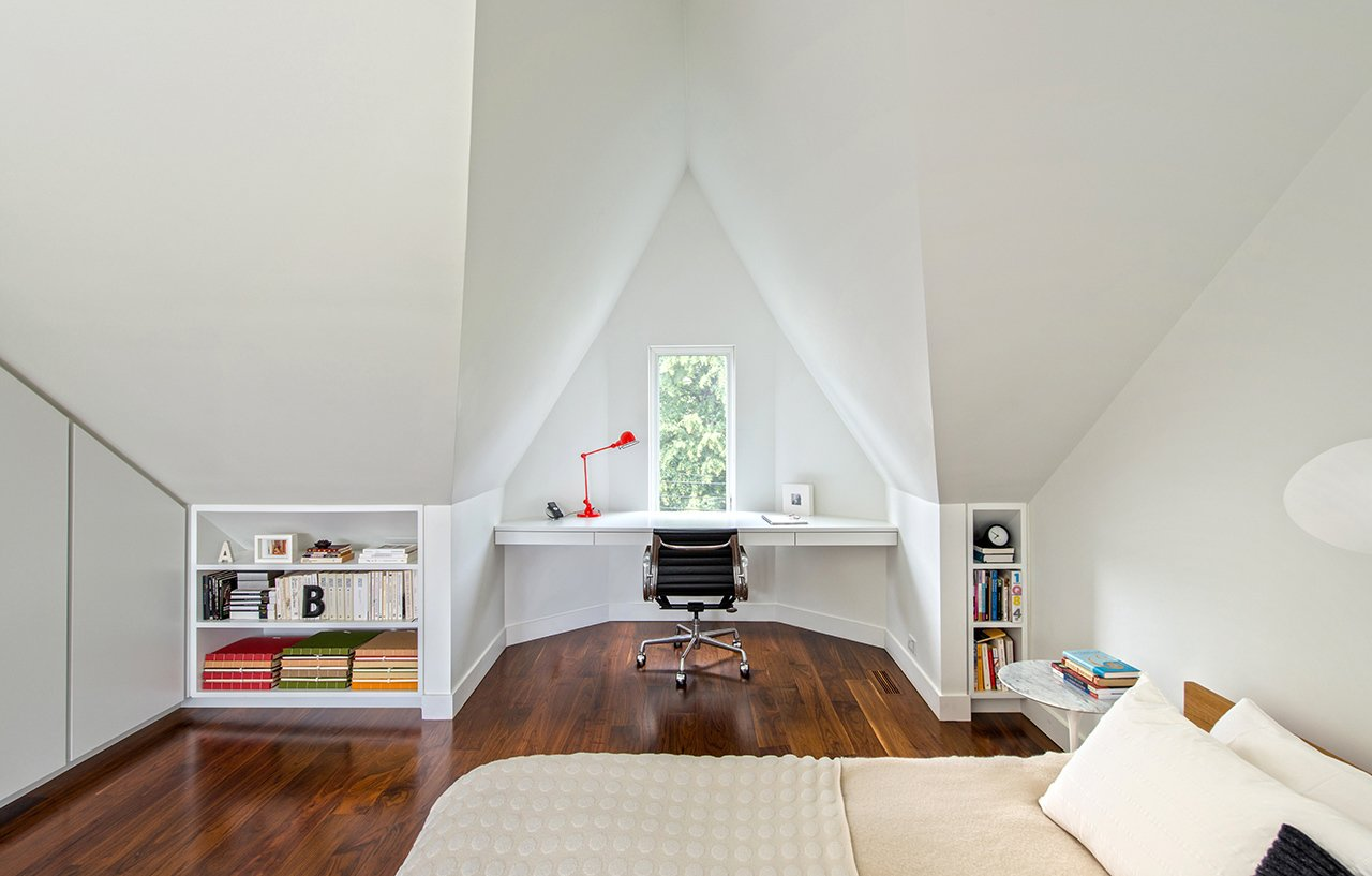 """I love the master bedroom, with the geometry of the white-painted, angled roof lines and the varying shadows that this creates,"" Dubbeldam says. The naturally lit space features built-in shelves and a floating desk that overlooks the street below through a tiny window. An aluminum Eames task chair and a Serge Mouille wall light adorn the space. Tagged: Bedroom, Bed, Chair, Table Lighting, and Medium Hardwood Floor.  Contrast House by Laura C. Mallonee from Modern Home Offices We Love"