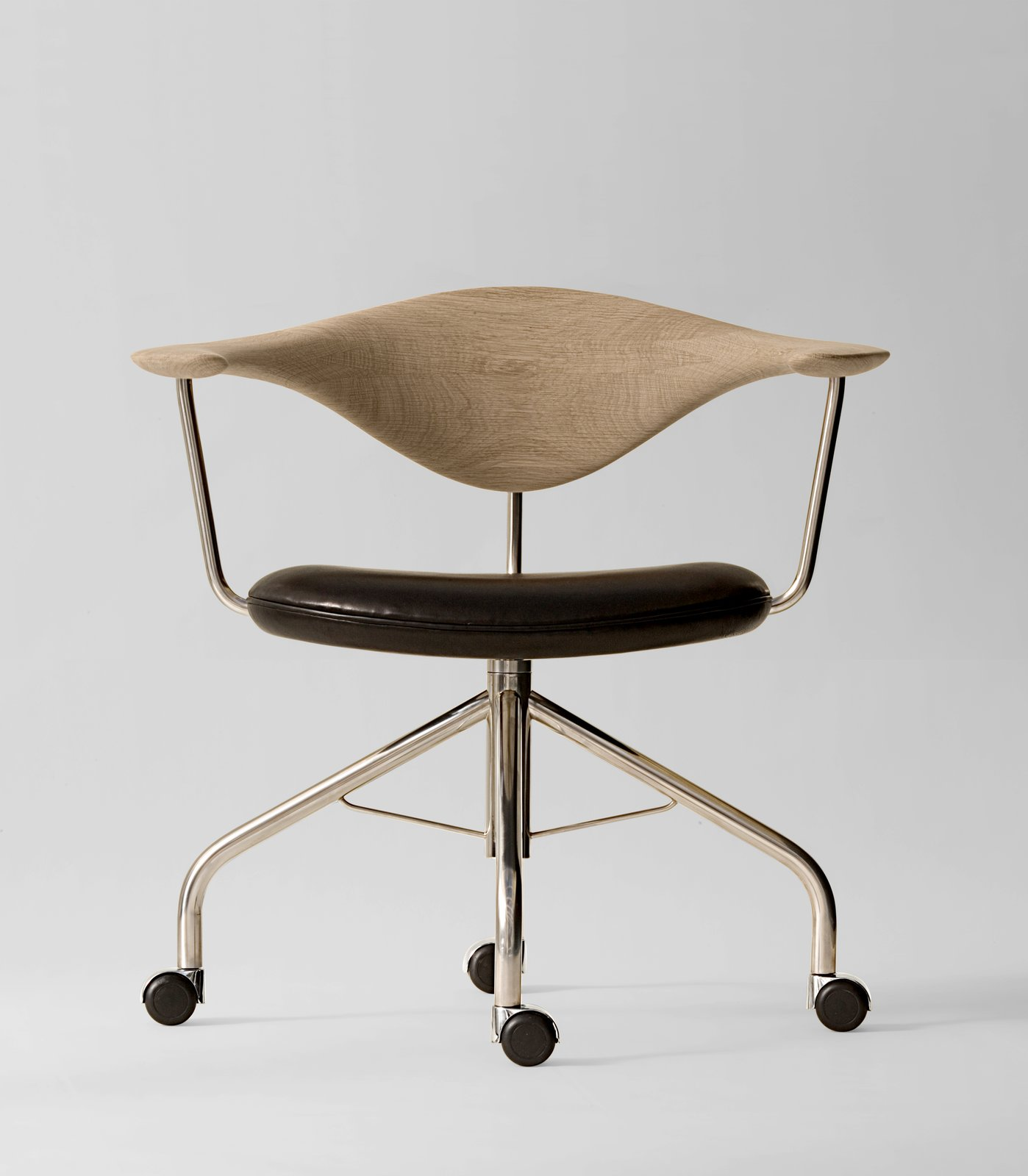 During a Danish furniture trade show, Dr. Eigill Snorrason critiqued the industry for not paying enough attention to ergonomics. The Swivel Chair (1955) Wegner's rejoinder of sorts, an elegant backrest of hand-carved wood that's been compared to a gently bent propeller. The smooth lines, thin profile and wheels invite a sure-footed slide across any office. Manufactured by PP Møbler. Photo by Jens Mourits Sørensen.  Photo 8 of 9 in 8 Iconic Chairs by Hans Wegner