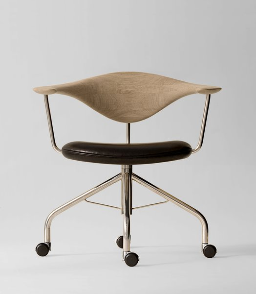 During a Danish furniture trade show, Dr. Eigill Snorrason critiqued the industry for not paying enough attention to ergonomics. The Swivel Chair (1955) Wegner's rejoinder of sorts, an elegant backrest of hand-carved wood that's been compared to a gently bent propeller. The smooth lines, thin profile and wheels invite a sure-footed slide across any office. Manufactured by PP Møbler. Photo by Jens Mourits Sørensen.