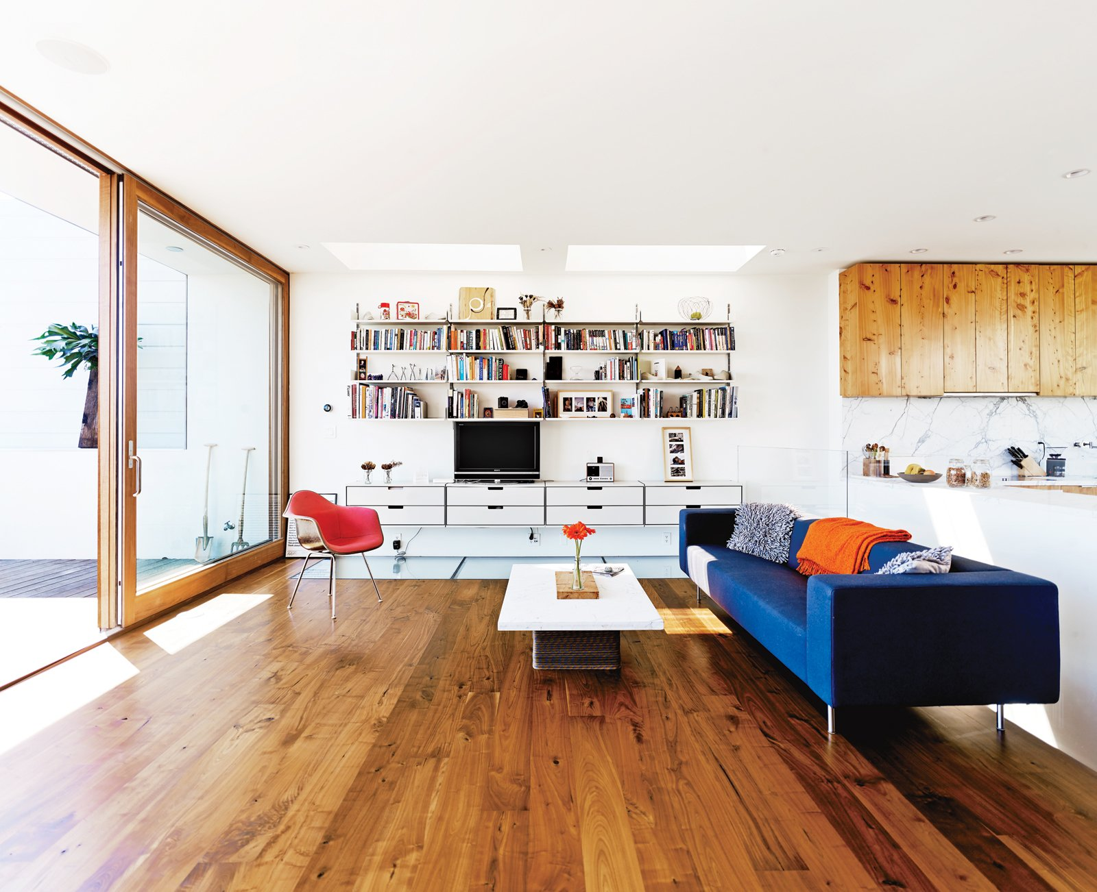 A 606 Universal Shelving System by Dieter Rams for Vitsoe hangs tough on the only opaque wall of the living room. Russell-Clarke and Moolsintong designed the coffee table, and Marcel Wanders gets credit for the Bottoni sofa for Moooi.  Photo 5 of 17 in Striking Slatted Wood and Glass Home in San Francisco