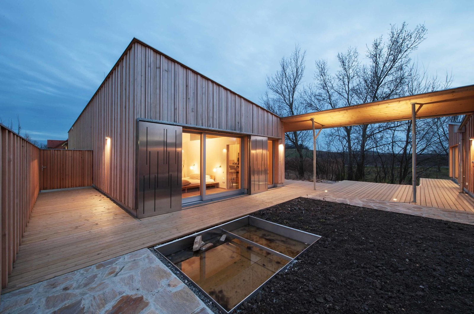 """The two buildings on either end of the house form an intimate, private courtyard between them — a common feature of farmhouses in the region. Within, a Mediterranean-style gravel garden designed by architect Joachim Kräftner offers an ideal spot for play and relaxation. Klauser calls it """"a walk-in sculpture.""""  Photo 7 of 7 in Peaceful Bungalow Makes for a Dream Retirement Home"""