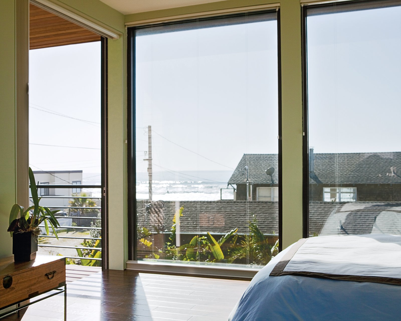 Floor-to-ceiling windows in the bedroom create the sensation of being outside, as if the entire house is one platform deck strategically shielded from the elements. A Modern Coastal Home in Stinson Beach - Photo 5 of 10