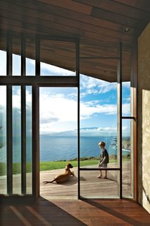 Clifftop House with Angled Roof in Maui - Photo 5 of 10 - Miha hangs out with Kea, the dog, on the wooden deck that extends the living space outdoors.