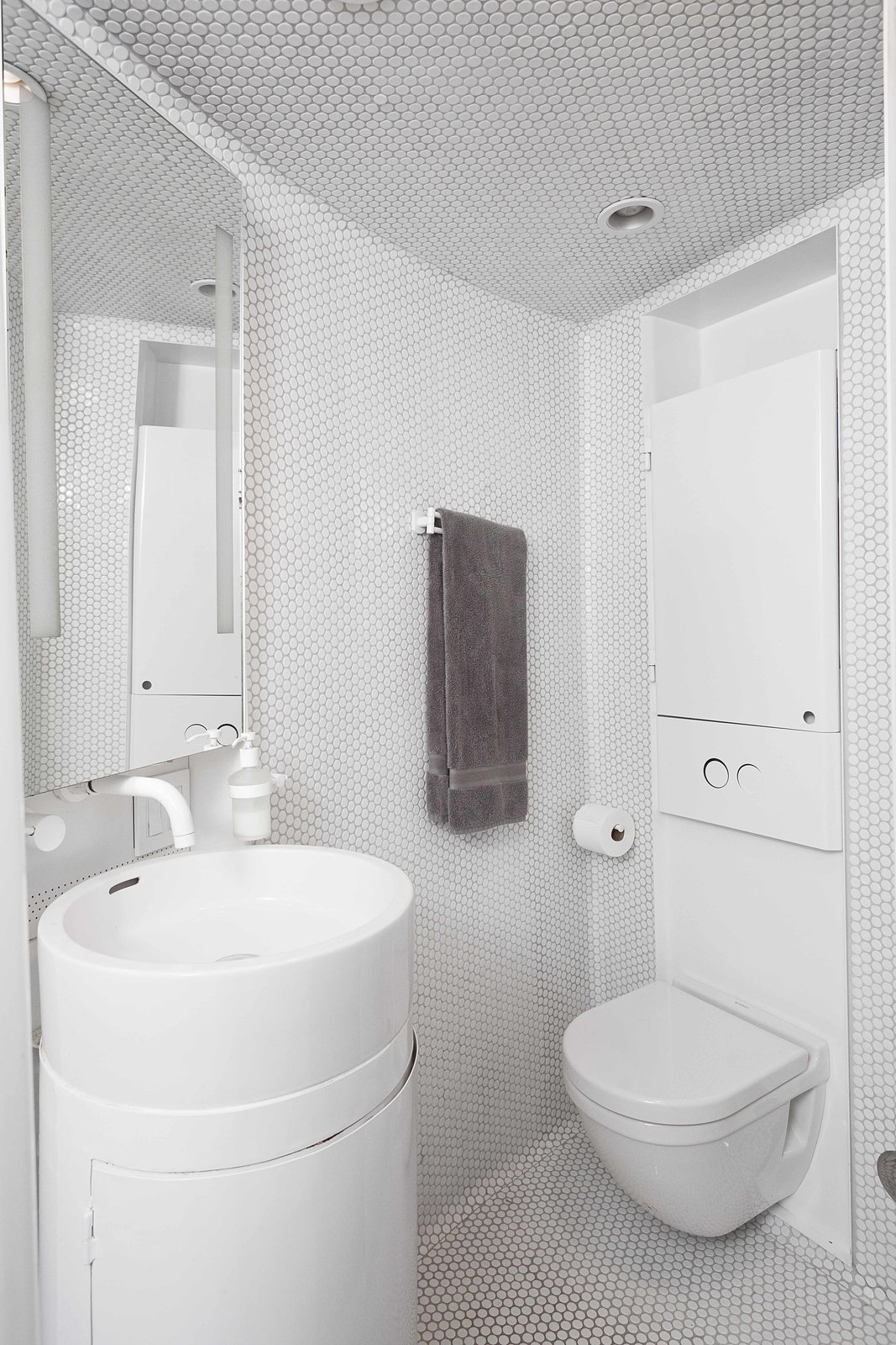 The bathroom features white ceramic glazed penny tile and a Duravit toilet with a custom vanity.