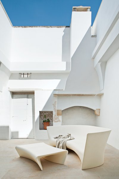 Modern Meets Ancient in a Renovated Italian Vacation Home - Photo 5 of 8 - A mix of polyethylene seating and rustic stonework is in the home's courtyard.