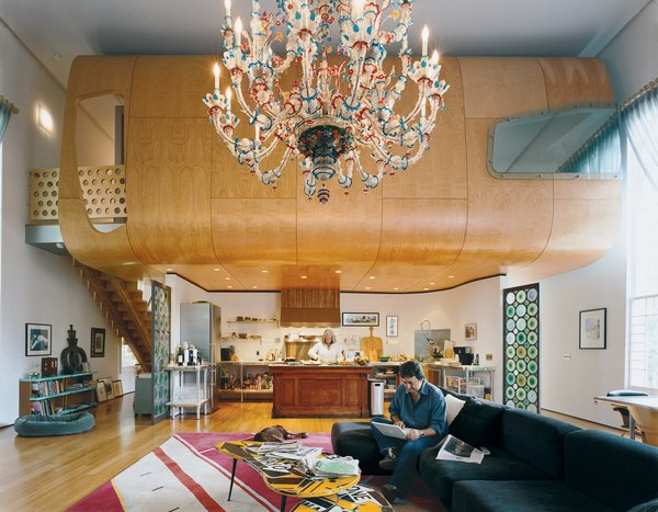 With the free-floating birch pod defining the space, and the massive Venetian chandelier accentuating the volume, the great room is, indeed, great. The Suarezes wanted the living area to be a place where the family could be occupied individually while still together. Bonnie works in the kitchen while Santiago (seated on an IKEA couch borrowed from one of their sons until they find something else) works on the computer.
