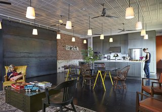 10 Remarkable Warehouse-to-Home Transformations - Photo 8 of 10 - In Auburn, Alabama, architect David Hill purchased a historic brick building that had served as a Baptist church, pool hall, and barbershop. When renovating the space's interior, Hill made an effort to retain its large, open spaces, and carefully restored the original metal ceiling tiles.