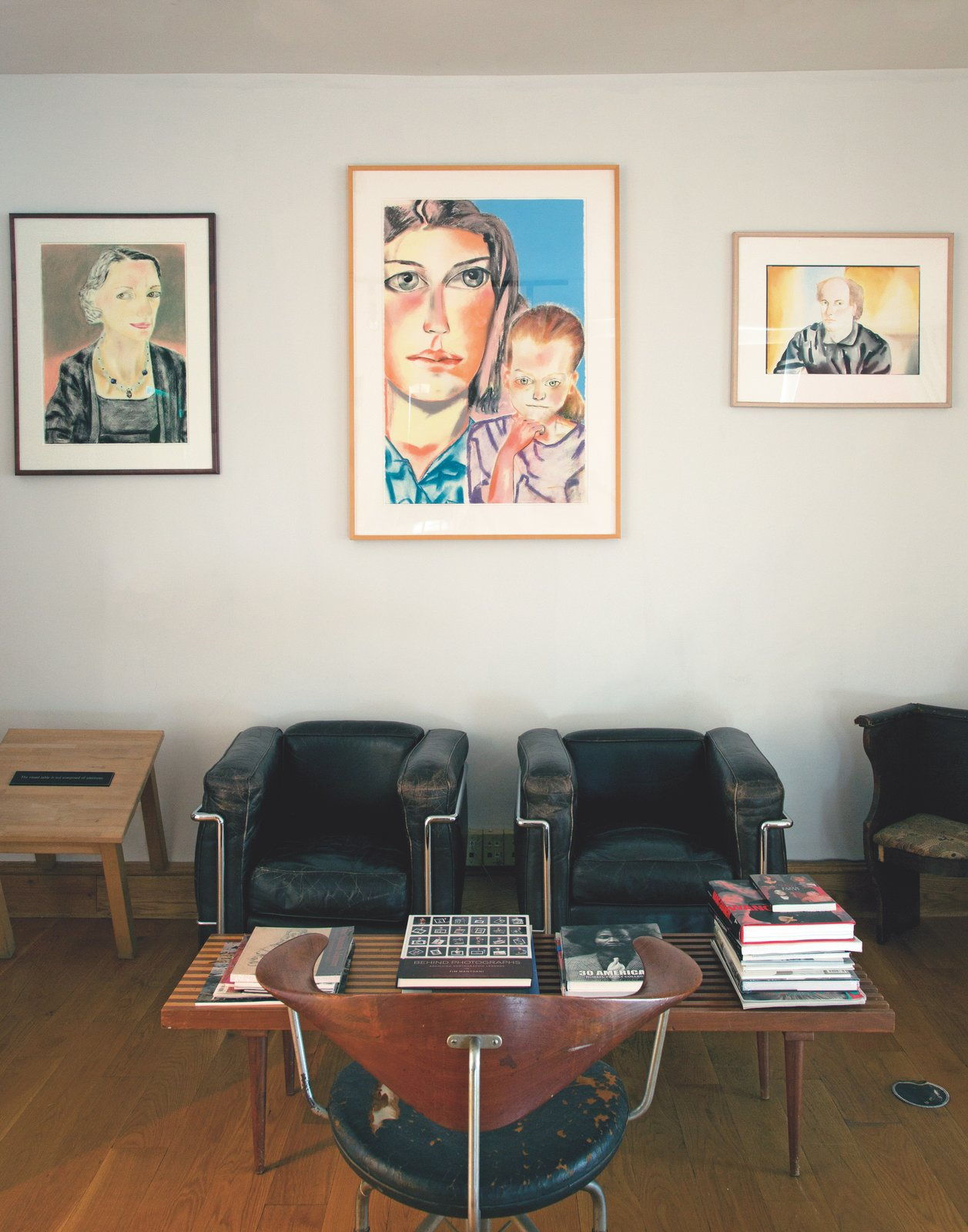 Timothy Greenfield-Sanders and his wife purchased a former church rectory in New York's East Village in 1978—years before the art scene exploded in the neighborhood. A series of family portraits by fellow artist Francesco Clemente hang above a reading area furnished with well-worn LC50 armchairs by Le Corbusier, a bench coffee table by George Nelson, and a rare Hans Wegner swivel chair. The side table to the left is a piece by conceptual artist Joseph Kosuth.  Heavenly Converted Churches by William Harrison