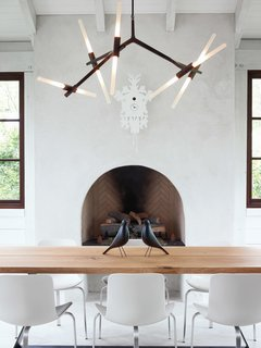 A Designer Brings Her Bold Brand of Texas Modern to this Atlanta Family Home - Photo 4 of 9 - The home's informal dining space has a slightly rustic feel, sporting bronze and wood in the form of a Lindsey Adams Adelman chandelier for Roll & Hill and a table by Terry Dwan, mixed with folk-art touches like the Eames House Birds and a cuckoo clock from Diamantini & Domeniconi. The PK8 chairs from Republic of Fritz Hansen were designed by Poul Kjærlholm and sourced from Kuhl-Linscomb in Houston, Texas.
