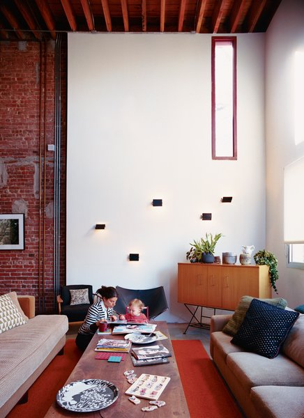 Darcy Miro and her son, Lucien, enjoy a moment in their new double-height living room. The Charlotte Perriand wall sconces are vintage finds.