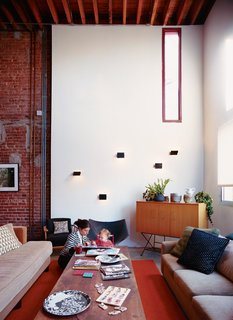 A House Grows in Brooklyn - Photo 1 of 5 - Darcy Miro and her son, Lucien, enjoy a moment in their new double-height living room. The Charlotte Perriand wall sconces are vintage finds.