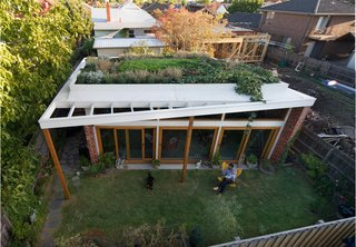 An Australian Architect's Simple Brick House With Impressive Green Roof - Photo 1 of 8 - Emilio Fuscaldo sits in the garden outside the brick house that he designed for himself and his partner, Anna Krien, on a small subdivided lot in Coburg, a suburb north of Melbourne, Australia. Photo by Nic Granleese.