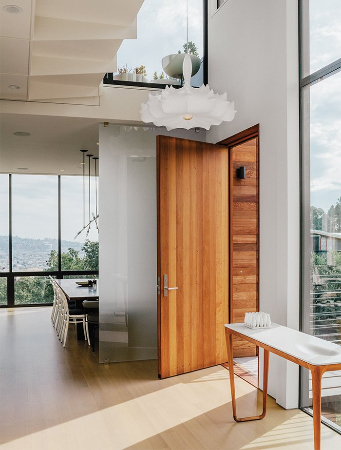 The entrance opens into a light-filled hall, with a Marcel Wanders chandelier and a Luna console table by Noé Duchaufour-Lawrance. Tagged: Doors, Exterior, Wood, and Swing Door Type.  Photo 5 of 19 in A Home with Eclectic Style Looks Just Right